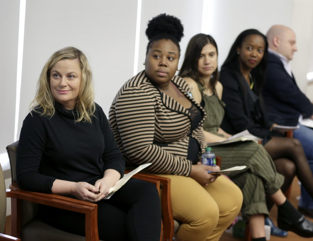 In this Feb. 20, 2018, photo, Amy Poehler, left, and others listen to speakers during a discussion about subminimum wage workers that depend on tips f