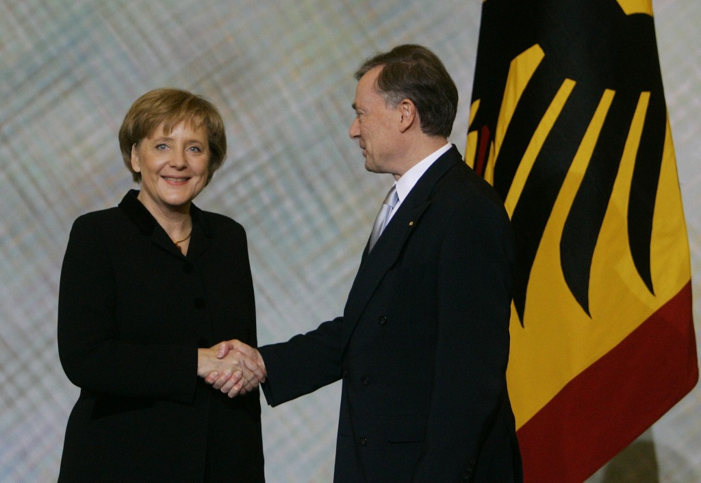 FILE - In this Nov. 22, 2005 file photo German President Horst Koehler, right, shakes hands with new German Chancellor Angela Merkel, left, at Charlot