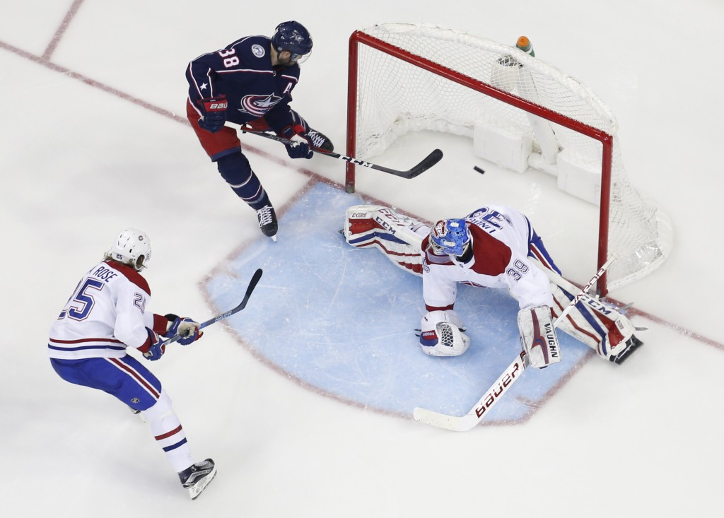 Columbus Blue Jackets' Boone Jenner, top, scores against Montreal Canadiens' Charlie Lindgren, right, as Jacob de la Rose, of Sweden, defends during t