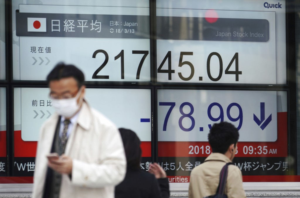 People walk past at an electronic stock board showing Japan's Nikkei 225 index at a securities firm in Tokyo Tuesday, March 13, 2018. Shares were mixe