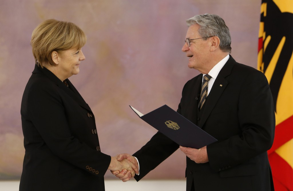 FILE - In this Dec. 17, 2013 file photo German President Joachim Gauck, rights, hands over the letter of appointment to newly reelected German Chancel