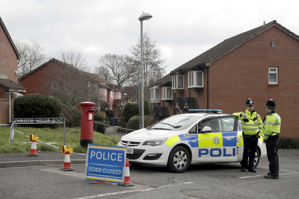 Police officers stand guard at the bottom of the road where former Russian double agent Sergei Skripal lives in Salisbury, England, Tuesday, March 13,