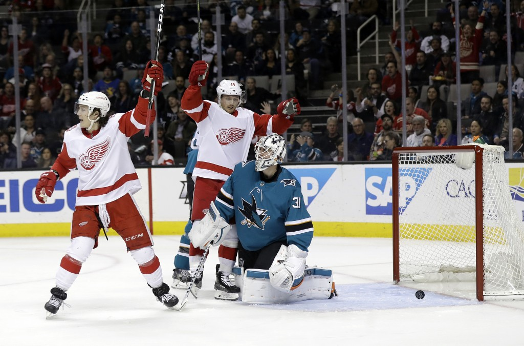 San Jose Sharks goaltender Martin Jones, center right, gives up a goal to Detroit Red Wings' Trevor Daley (not shown) as Red Wings' Tyler Bertuzzi, le