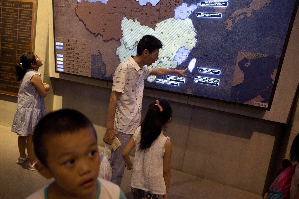 "FILE -  In this  Aug. 2, 2017, file photo, a man points out Taiwan to a young girl on a display titled: ""Humiliation in the history of the Chinese nat"