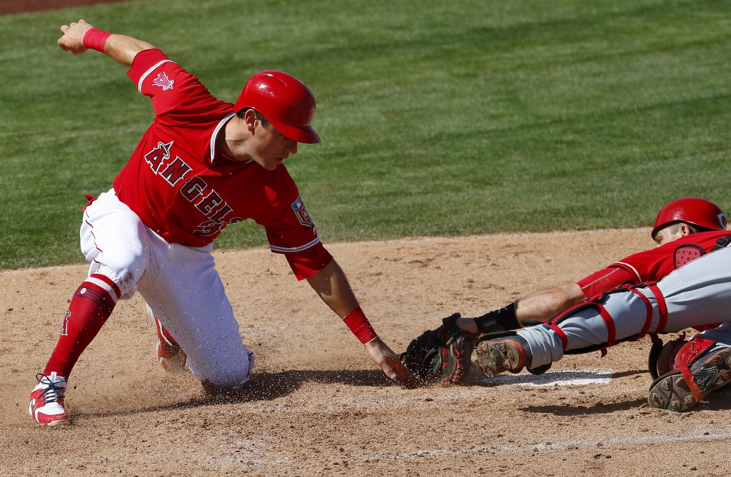 Los Angles Angels' Ian Kindler, left, slides safely across the plate as Cincinnati Reds catcher Devin Mesoraco reaches with a late tag during the thir