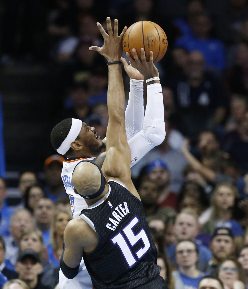 Oklahoma City Thunder forward Carmelo Anthony, top, is fouled by Sacramento Kings guard Vince Carter (15) as he shoots in the first half of an NBA bas