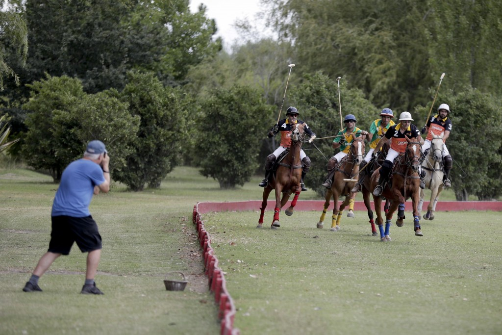In this Feb. 27, 2018 photo, Jed Hulsey, from Newport Beach, California, right, takes a photo of a polo match at La Carona club, Capilla del Senor, Bu