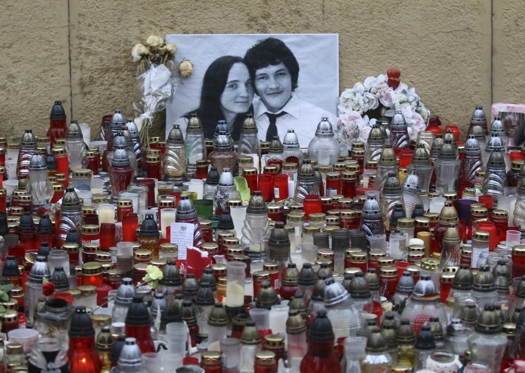 FILE - In this Friday, March 9, 2018 file photo Candles are placed in front of a photo of journalist Jan Kuciak and his fiancee Martina Kusnirova  dur