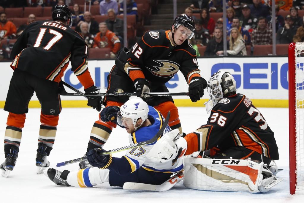 St. Louis Blues' Jaden Schwartz, bottom center, is shoved by Anaheim Ducks' Josh Manson in front of Ducks goalie John Gibson during the first period o