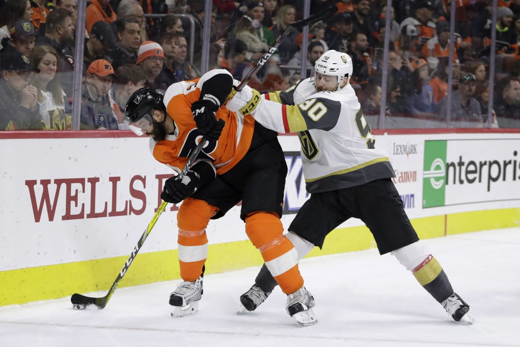 Vegas Golden Knights' Tomas Tatar, right, and Philadelphia Flyers' Radko Gudas battle for the puck during the third period of an NHL hockey game, Mond
