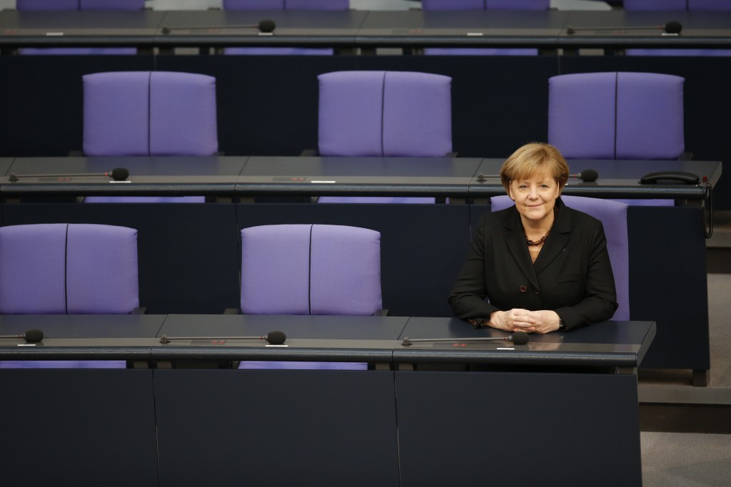 FILE - In this Dec. 17, 2013 file photo German Chancellor Angela Merkel sits smiling at the government bench after being reelected during a meeting of