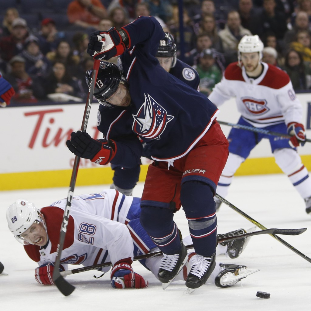 Columbus Blue Jackets' Cam Atkinson, front right, takes the puck away from Montreal Canadiens' Mike Reilly during the second period of an NHL hockey g