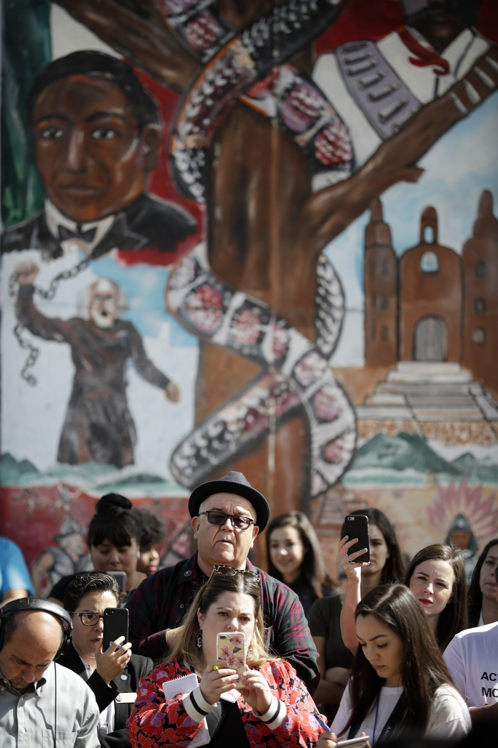 People look on in front of a mural depicting heroes of the Mexican revolution during a rally against a scheduled upcoming visit to the area by Preside