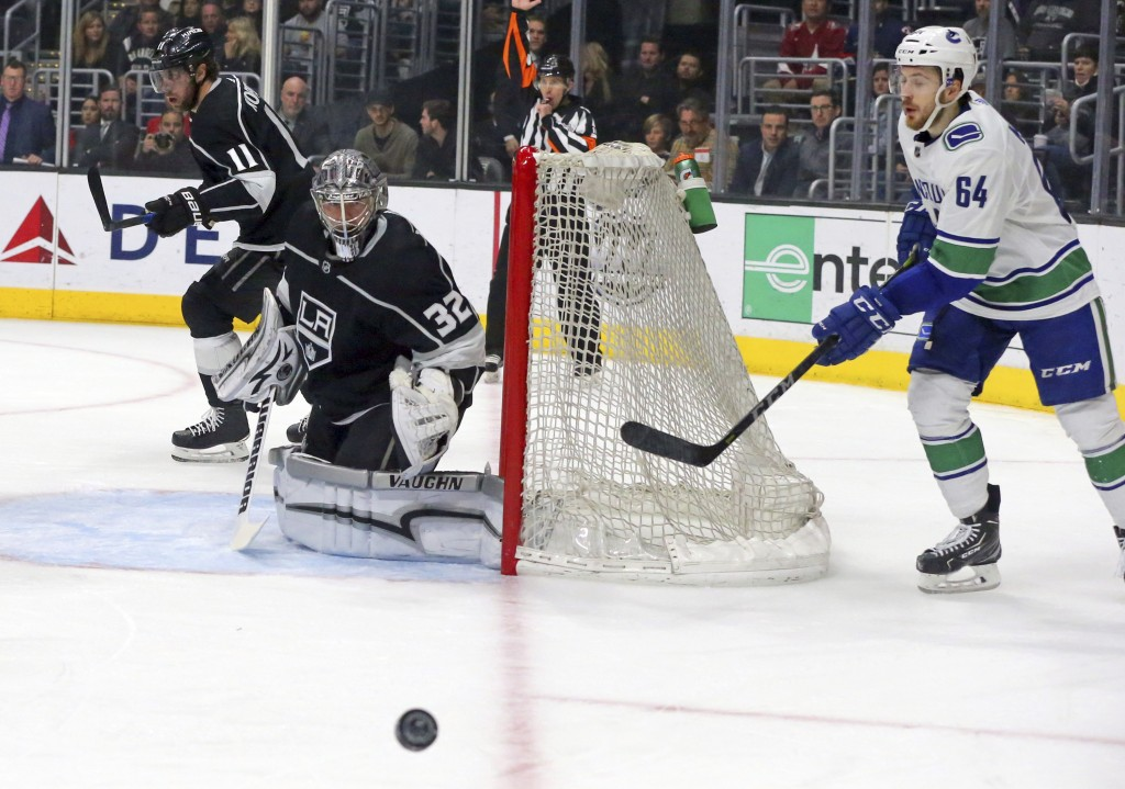 Vancouver Canucks center Tyler Motte (64) skates behind Los Angeles Kings goalie Jonathan Quick (32) in the first period of an NHL hockey game in Los