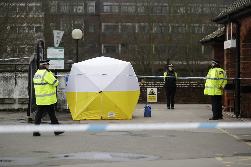Police officers guard a cordon around a police tent covering a supermarket car park pay machine near the area where former Russian double agent Sergei