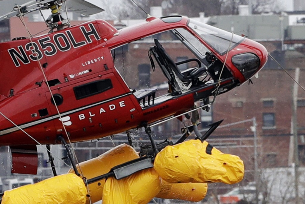 A helicopter is hoisted by crane from the East River onto a barge, Monday, March 12, 2018, in New York. The pilot was able to escape the Sunday night