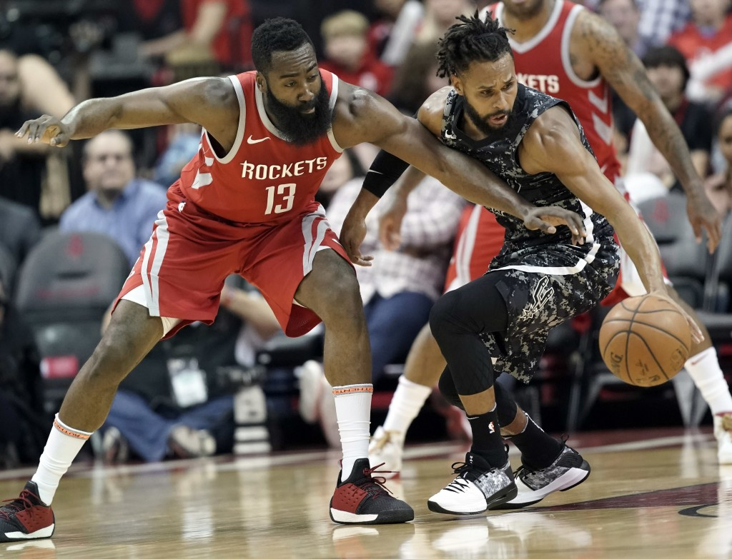 Houston Rockets' James Harden (13) tries to steal the ball from San Antonio Spurs' Patty Mills during the first half of an NBA basketball game Monday,