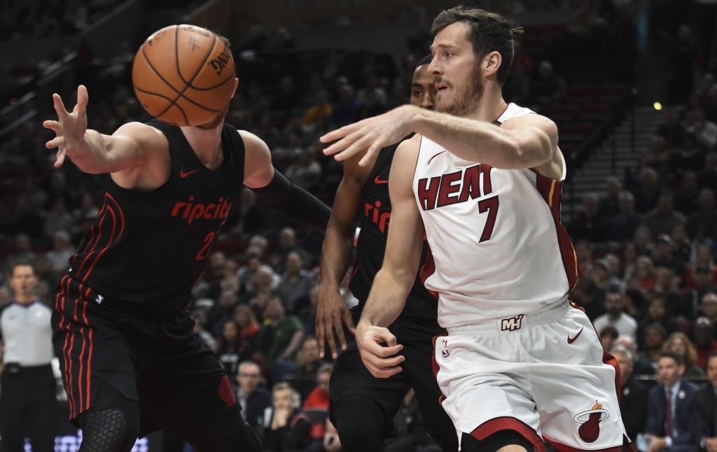 Miami Heat guard Goran Dragic passes the ball on Portland Trail Blazers center Jusuf Nurkic during the first half of an NBA basketball game in Portlan