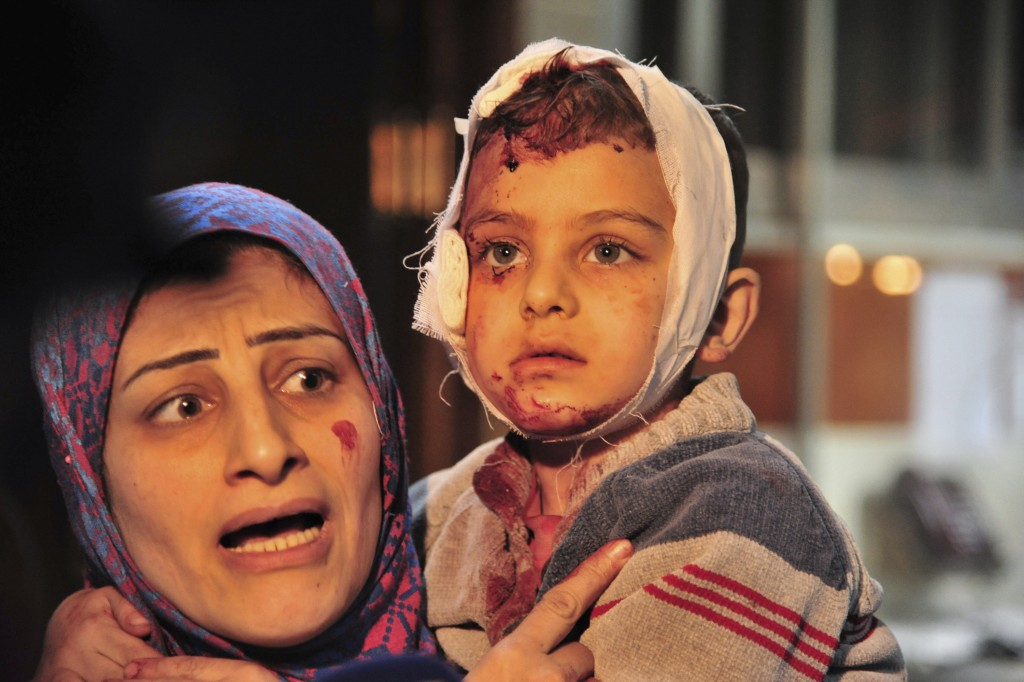 FILE In this file photo released Feb. 21, 2016, by the Syrian official news agency SANA, a woman carries a child injured in a triple blast claimed by