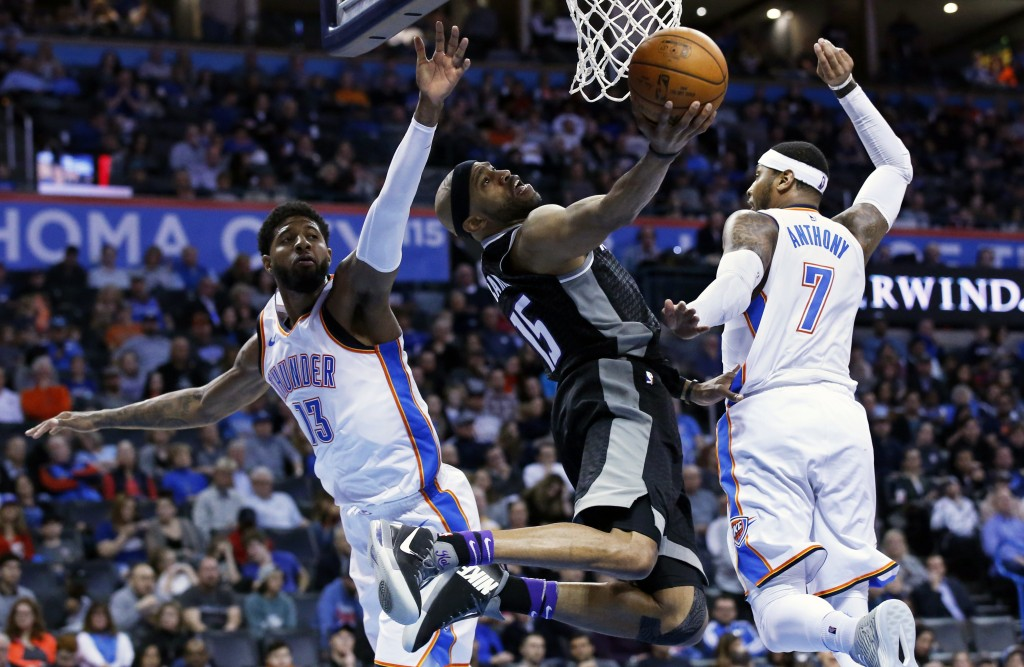 Sacramento Kings guard Vince Carter (15) shoots between Oklahoma City Thunder forwards Paul George (13) and Carmelo Anthony (7) in the first half of a