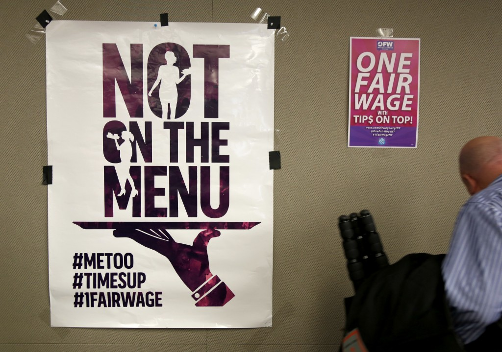 In this Feb. 20, 2018, photo, signs supporting fair wages and treatment are displayed at a discussion about subminimum wage workers that depend on tip