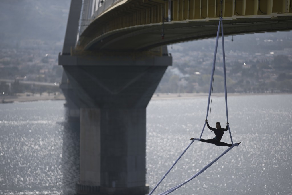 Aerial Dancer Katerina Soldatou performes suspended from the Rio-Antirrio bridge in southern Greece, on Monday, March 12, 2018. Soldatou says her perf