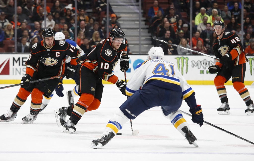 Anaheim Ducks' Corey Perry, center, moves the puck under pressure by St. Louis Blues' Robert Bortuzzo during the second period of an NHL hockey game M