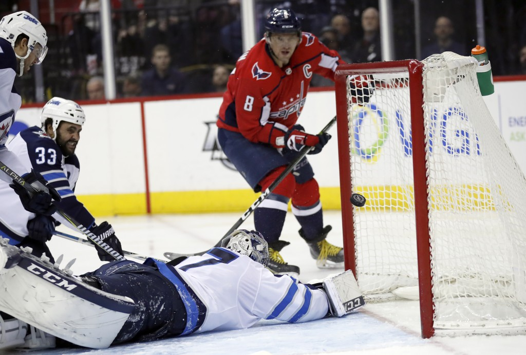 Washington Capitals left wing Alex Ovechkin (8) watches his shot get past Winnipeg Jets goaltender Connor Hellebuyck (37) for a goal in the second per