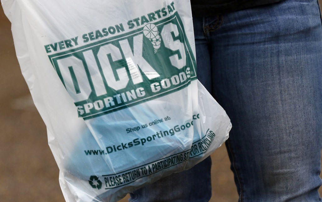 FILE- In this March 1, 2018, file photo a customer carries her purchase from a Dick's Sporting Goods store in Madison, Miss. Dick's Sporting Goods, In