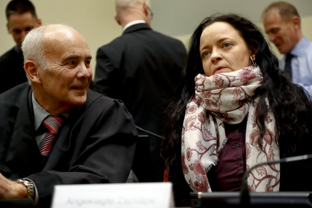 Terror suspect Beate Zschaepe, right, sits in a court room beside her lawyer Hermann Borchert, left, in Munich, Germany, Tuesday, March 13, 2018. Germ