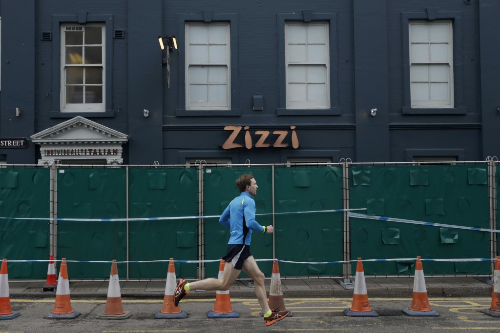 A man runs past a fence cordoning off Zizzi restaurant near the area where former Russian double agent Sergei Skripal and his daughter were found crit