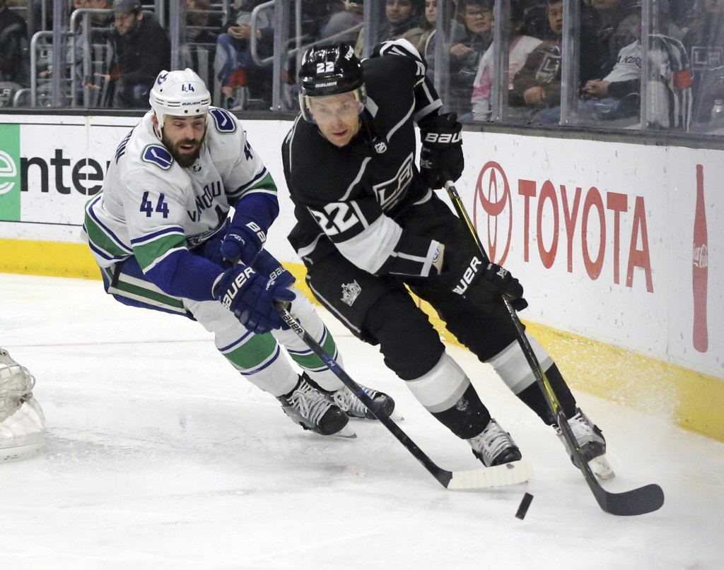 Los Angeles Kings center Trevor Lewis (22) and Vancouver Canucks defenseman Erik Gudbranson (44) chase the puck in the second period of an NHL hockey