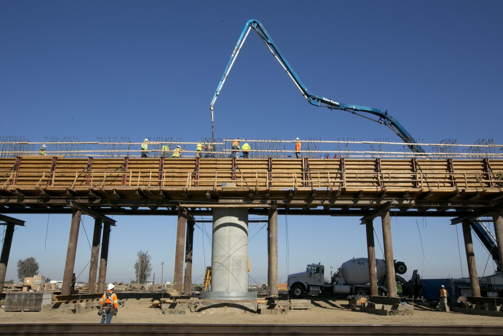 FILE - In this Dec. 6, 2017, file, workers pour concrete on to one of the elevated sections of the high-speed rail that will cross over the San Joaqui