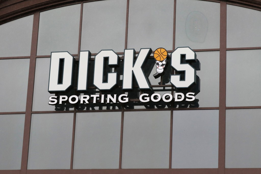 FILE- In this March 1, 2018, file photo, a sign for Dick's Sporting Goods store is displayed at the store in Madison, Miss. Dick's Sporting Goods, Inc