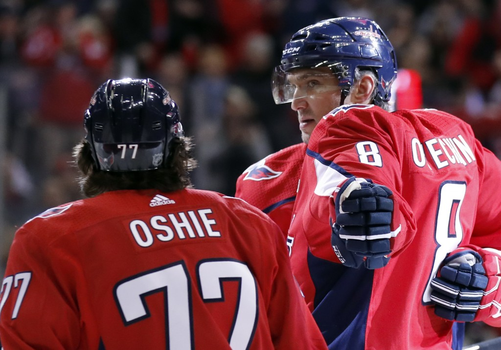 Washington Capitals left wing Alex Ovechkin (8) reaches to celebrate with right wing T.J. Oshie (77) after scoring in the first period of an NHL hocke