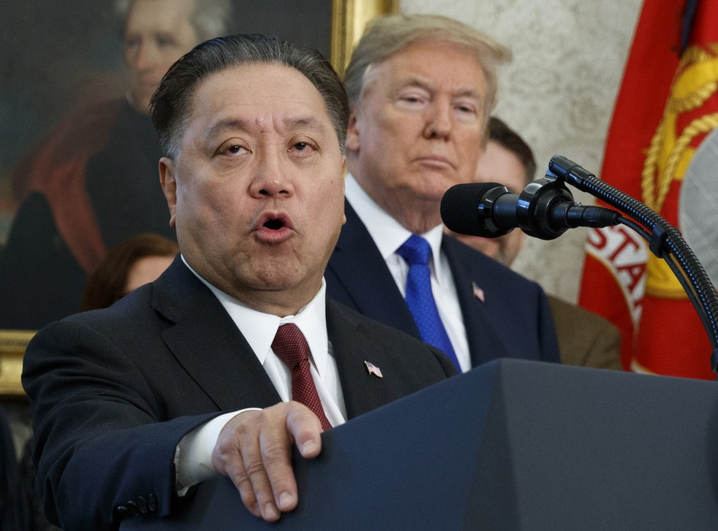 FILE - In this Thursday, Nov. 2, 2017, file photo, Broadcom CEO Hock Tan speaks while U.S. President Donald Trump listens, in background, during an ev