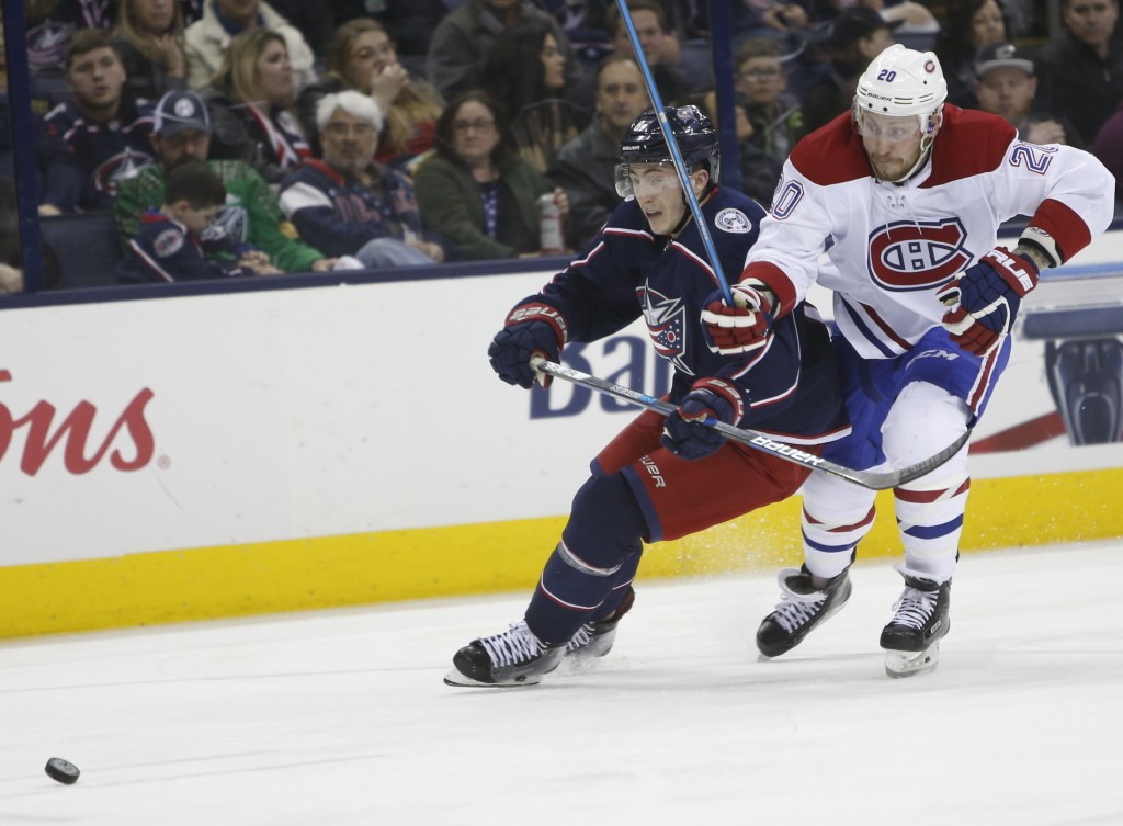 Columbus Blue Jackets' Zach Werenski, left, and Montreal Canadiens' Nicolas Deslauriers chase the puck during the third period of an NHL hockey game M