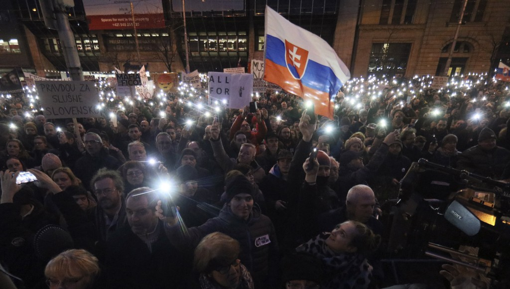 FILE - In this Friday, March 9, 2018 file photo, demonstrators hold up their smartphones during an anti-government rally in Bratislava, Slovakia. Slov