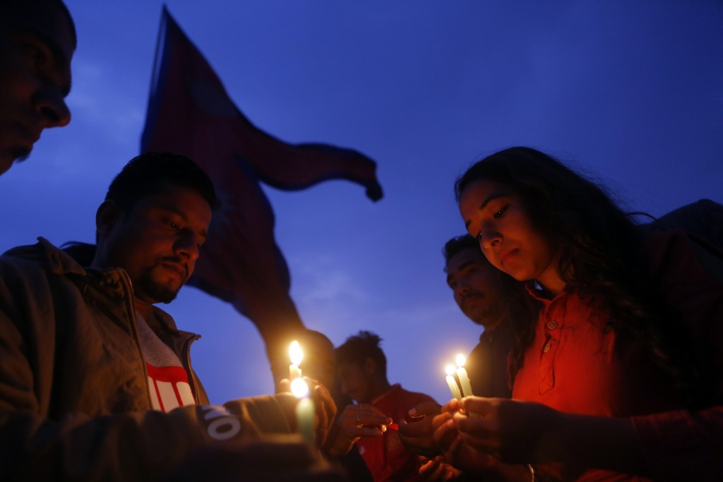 Nepalese people light candles to pay tribute to those who died in Monday's plane crash in Kathmandu, Nepal, Tuesday, March 13, 2018. (AP Photo/Niranja