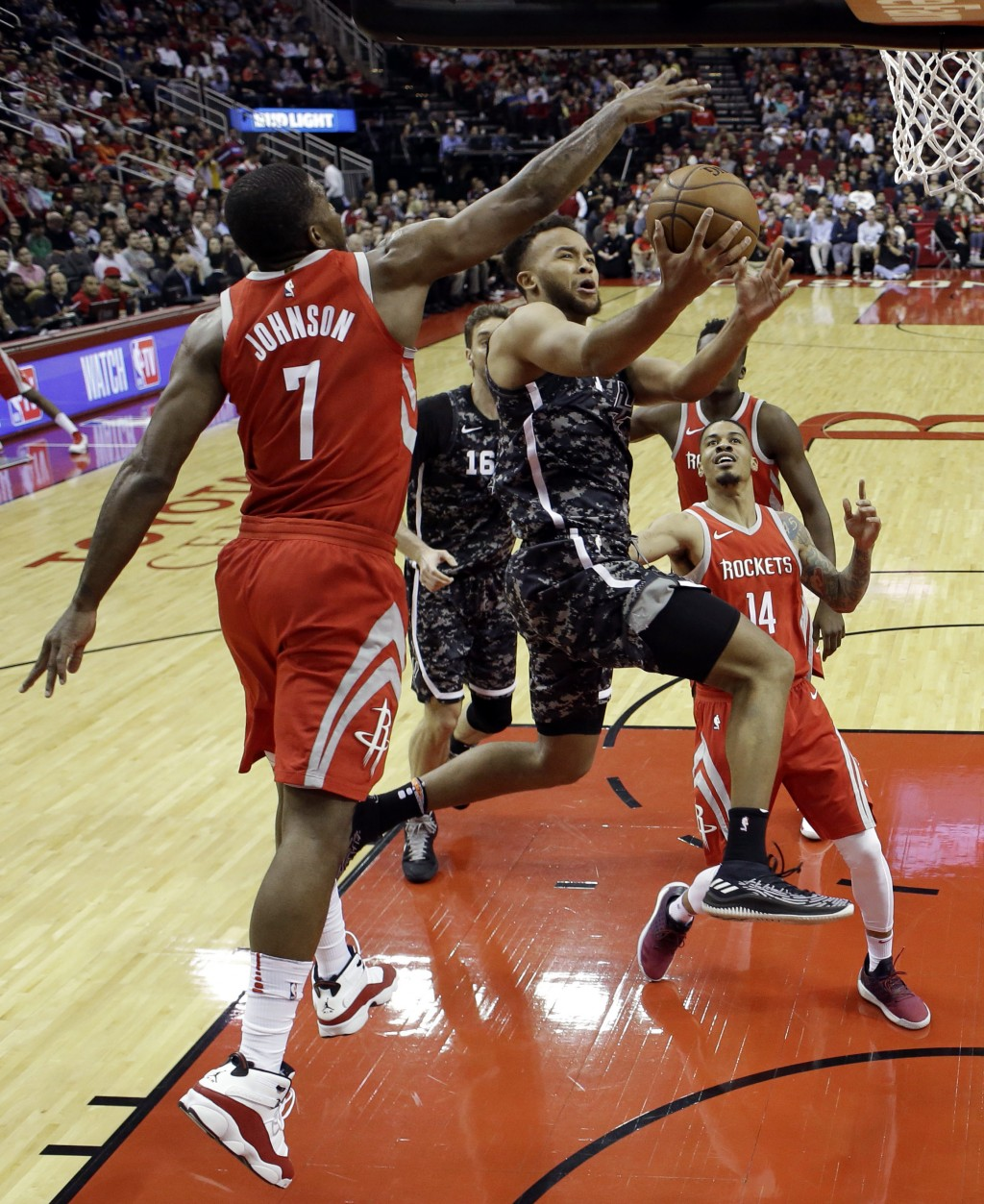 San Antonio Spurs' Kyle Anderson, center, goes up to shoot as Houston Rockets' Joe Johnson (7) defends during the first half of an NBA basketball game