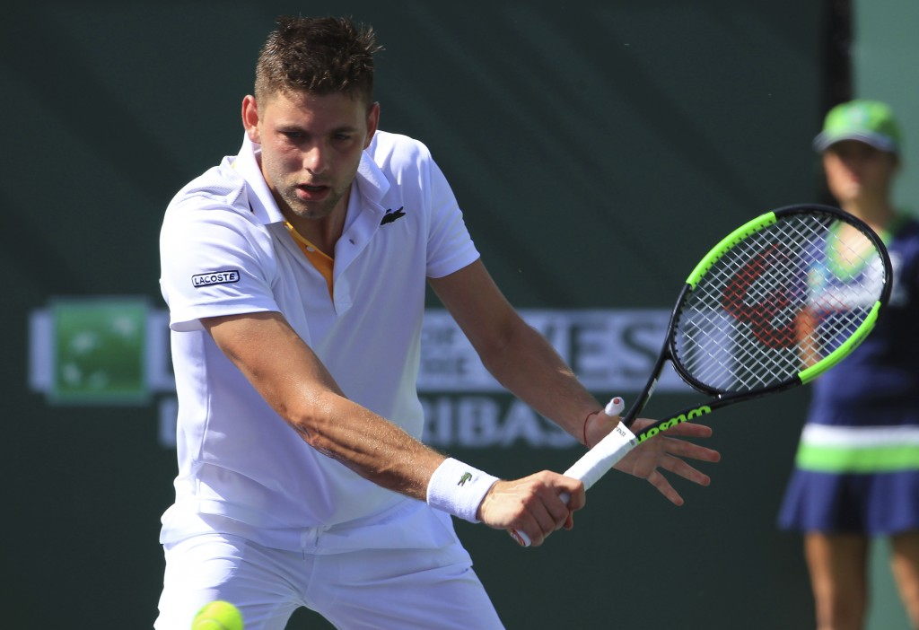 Filip Krajinovic returns a shot to Roger Federer during the third round of the BNP Paribas Open tennis tournament at the Indian Wells Tennis Garden in