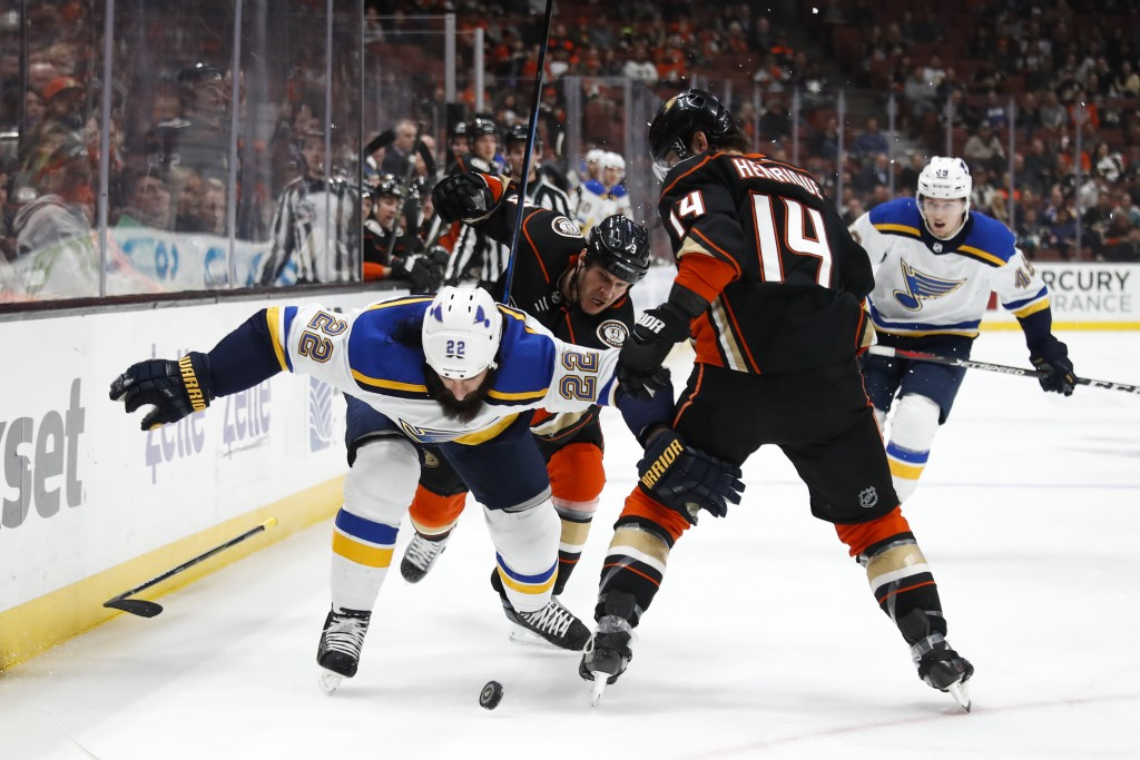 St. Louis Blues' Chris Thorburn, left, drops his stick while fighting for the puck with Anaheim Ducks' Adam Henrique during the first period of an NHL