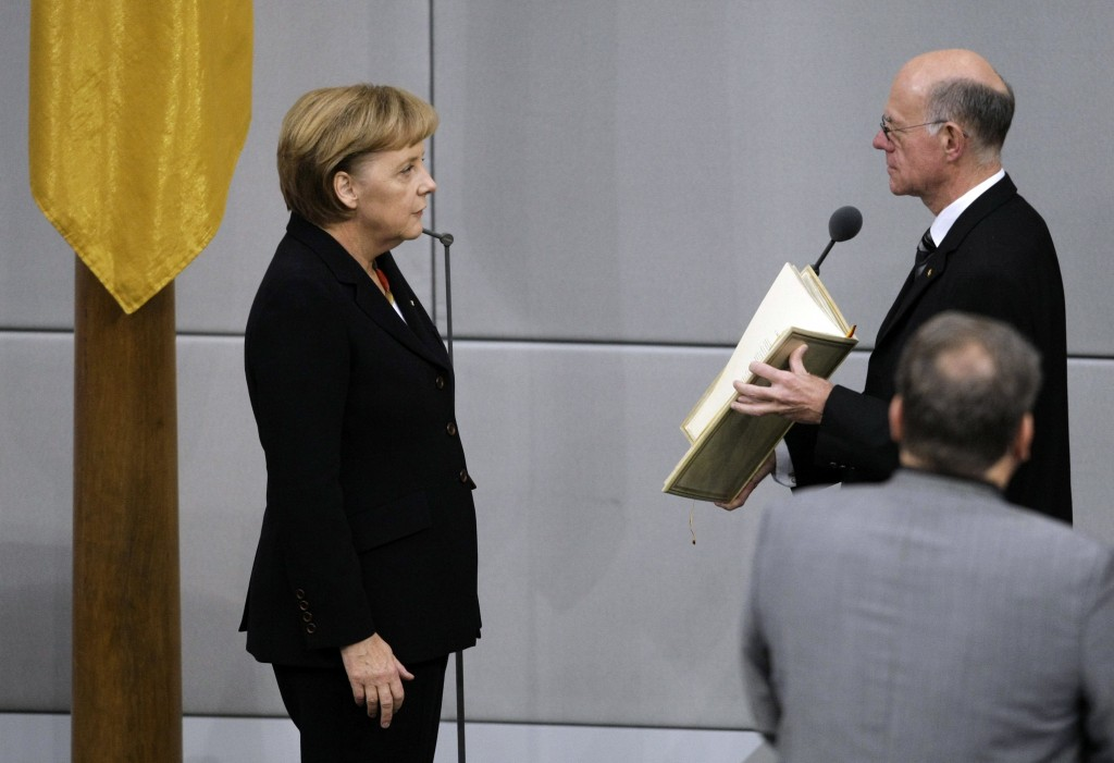 FILE - In this Oct. 28, 2009 file photo reelected German chancellor Angela Merkel, left, takes the oath of office in the parliament in Berlin, Germany