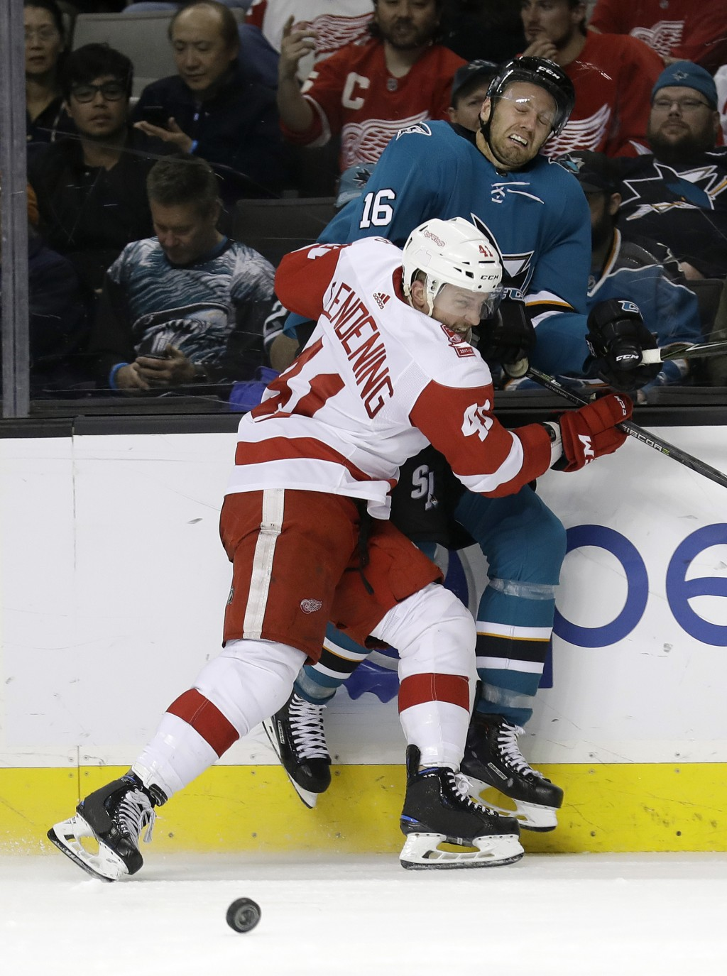 Detroit Red Wings' Luke Glendening (41) presses San Jose Sharks' Eric Fehr (16) against the boards during the second period of an NHL hockey game, Mon
