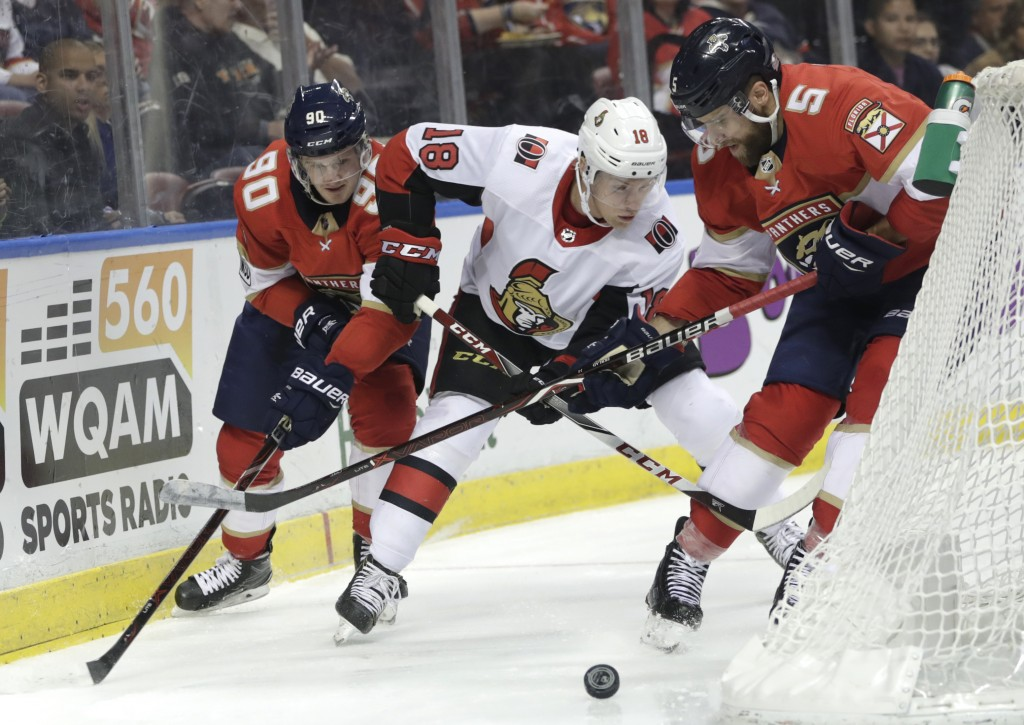 Florida Panthers' Jared McCann (90) and Aaron Ekblad (5) go for the puck against Ottawa Senators' Ryan Dzingel (18) during the second period of an NHL