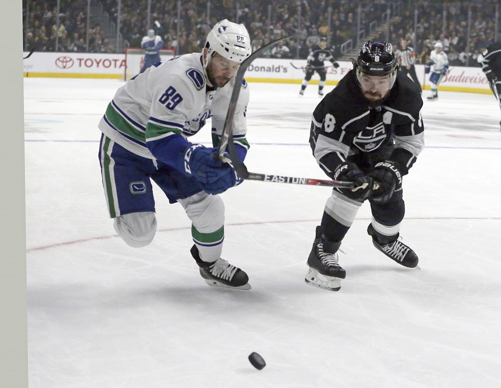 Vancouver Canucks center Sam Gagner (89) and Los Angeles Kings defenseman Drew Doughty (8) chase the puck in the first period of an NHL hockey game in