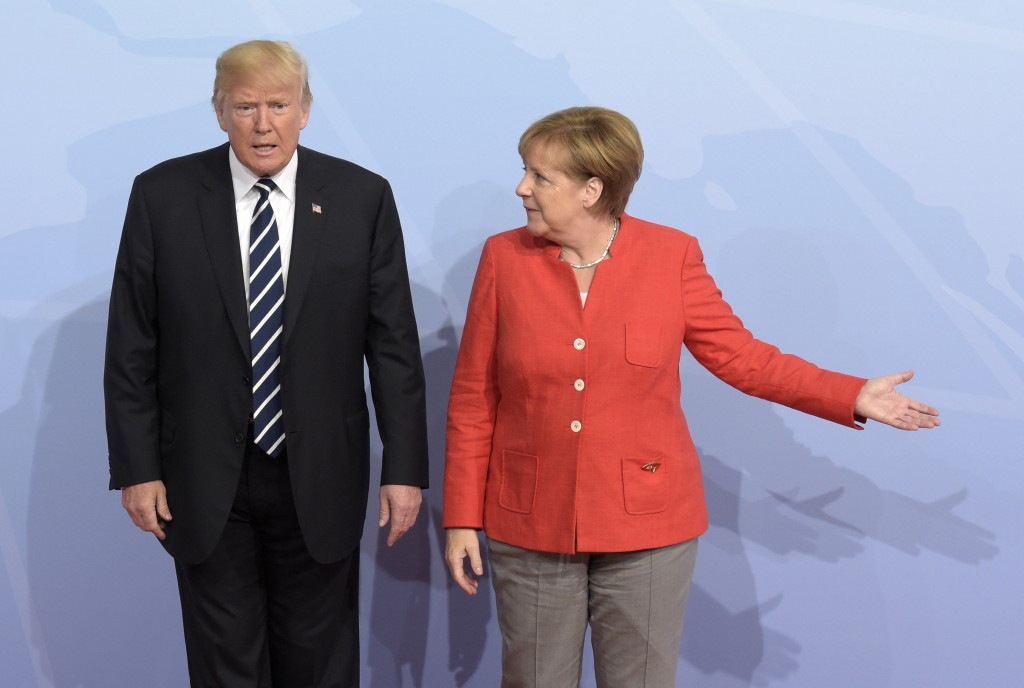 FILE - In this July 7, 2017 file photo U.S. President Donald Trump, left, is welcomed by German Chancellor Angela Merkel on the first day of the G-20