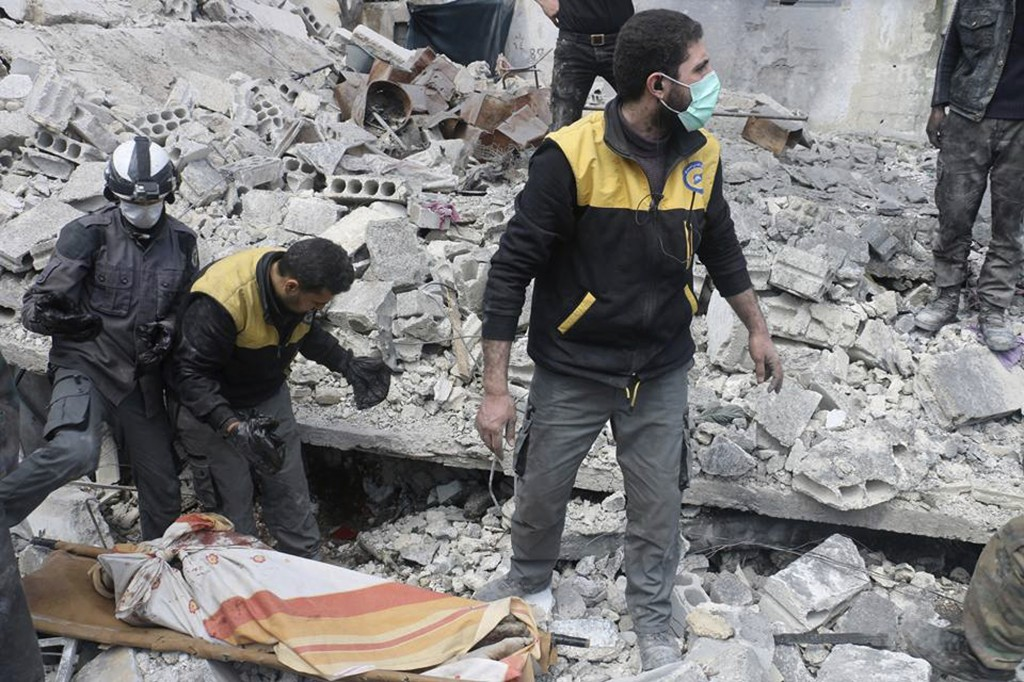This photo released Tuesday, March 13, 2018, by the Syrian Civil Defense group known as the White Helmets, shows members of the White Hemets removing