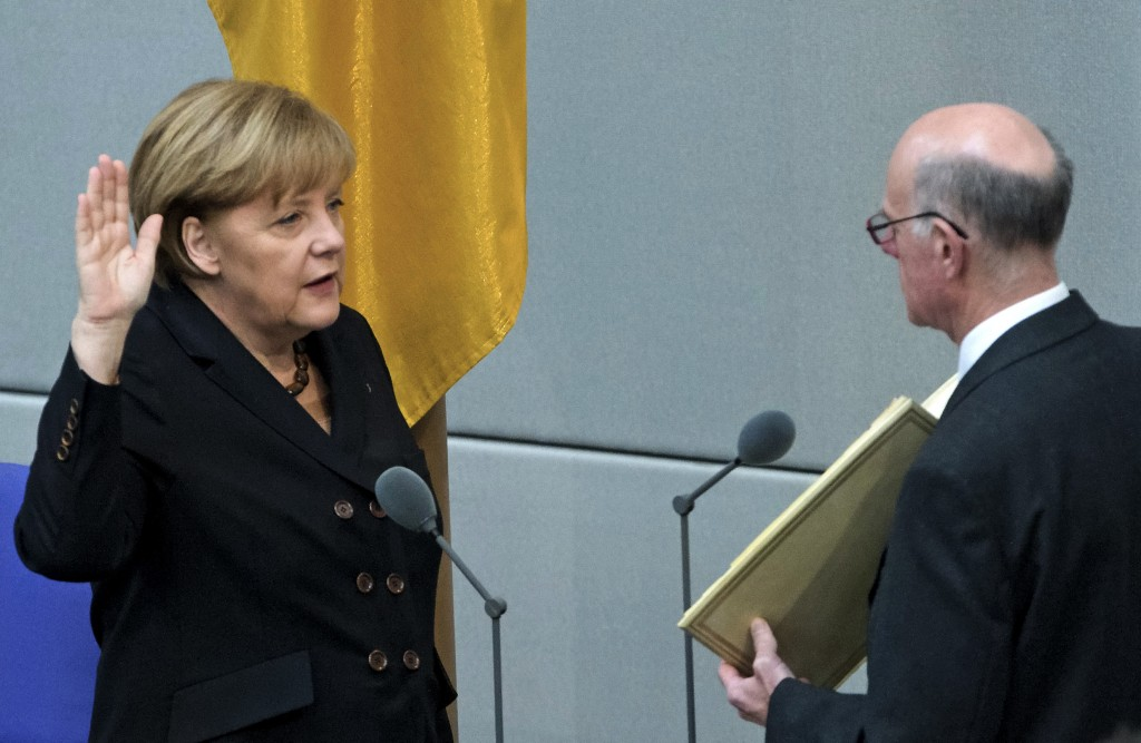 FILE - In this Dec. 17, 2013 file photo German Chancellor Angela Merkel, left, takes the oath of office by President of the Federal Parliament, Norber