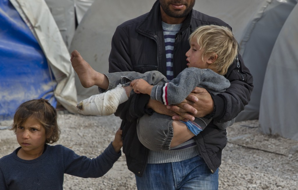 FILE - In this Nov. 16, 2014 file photo, a Syrian Kurdish refugee from the Kobani area carries an injured child at a camp in Suruc, on the Turkey-Syri